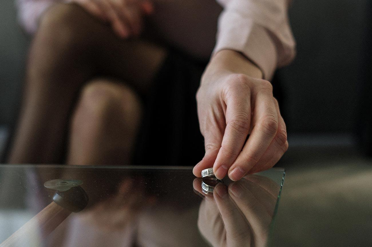 woman's hand placing wedding band on table